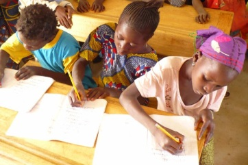 School Girls Unite scholars writing at a desk in Mali