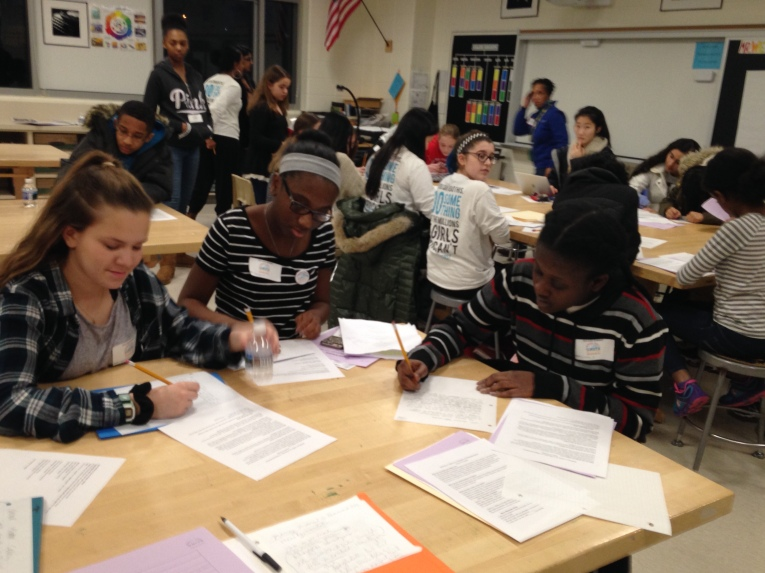 Photo of middle school members of School Girls Unite writing letters.