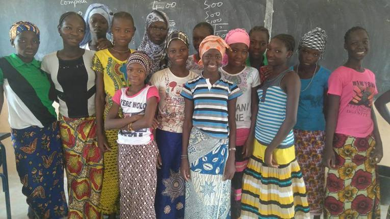Photo of School Girls Unite scholarship students smiling in front of a chalkboard.